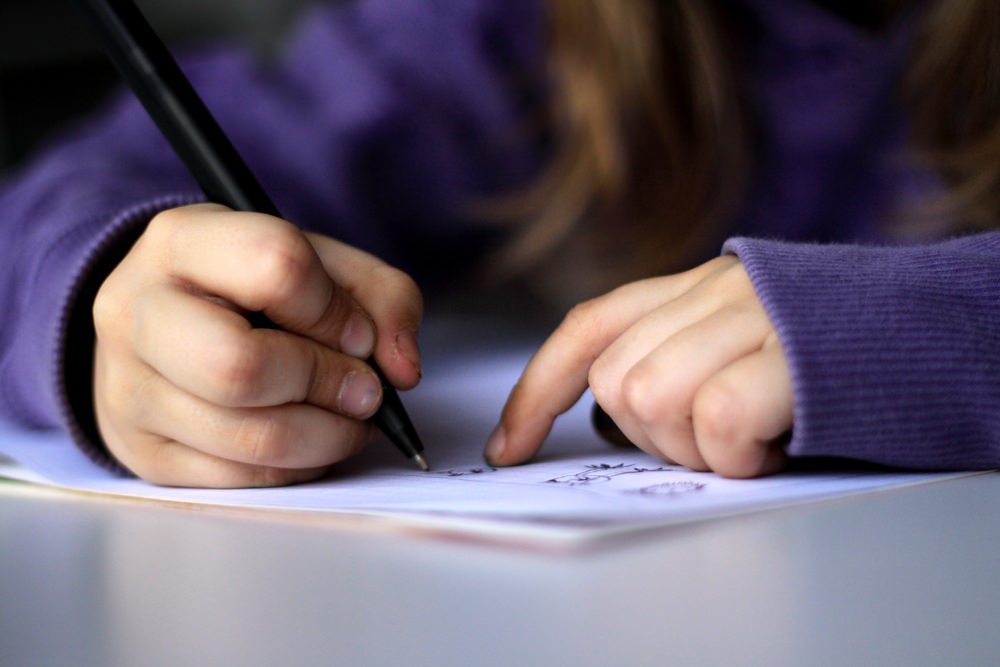 Image: Student writing, gratitude journaling in the classroom