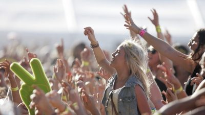Image: A woman in a crowd that is joyous reaching up happily