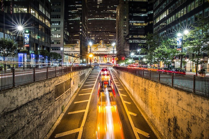 Image: traffic emerging from a tunnel in a city at night with lights moving across the image