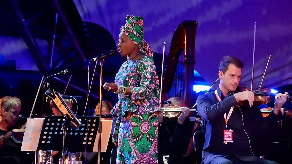 Image: Angelique Kidjo singing on stage with an orchestra