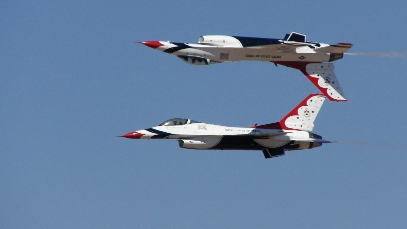 Image: Two fighter jets , one flying above the other, up side down