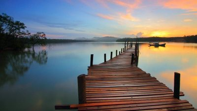 Image: A very long dock reaching out into water at sunrise