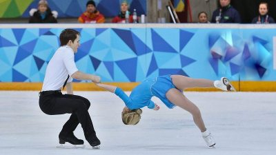 Image: Skating pair with man working very hard and woman in a death spiral