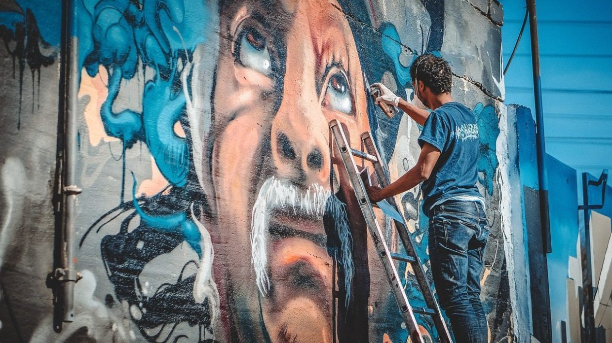 Image: A man on a ladder painting graffiti on a wall