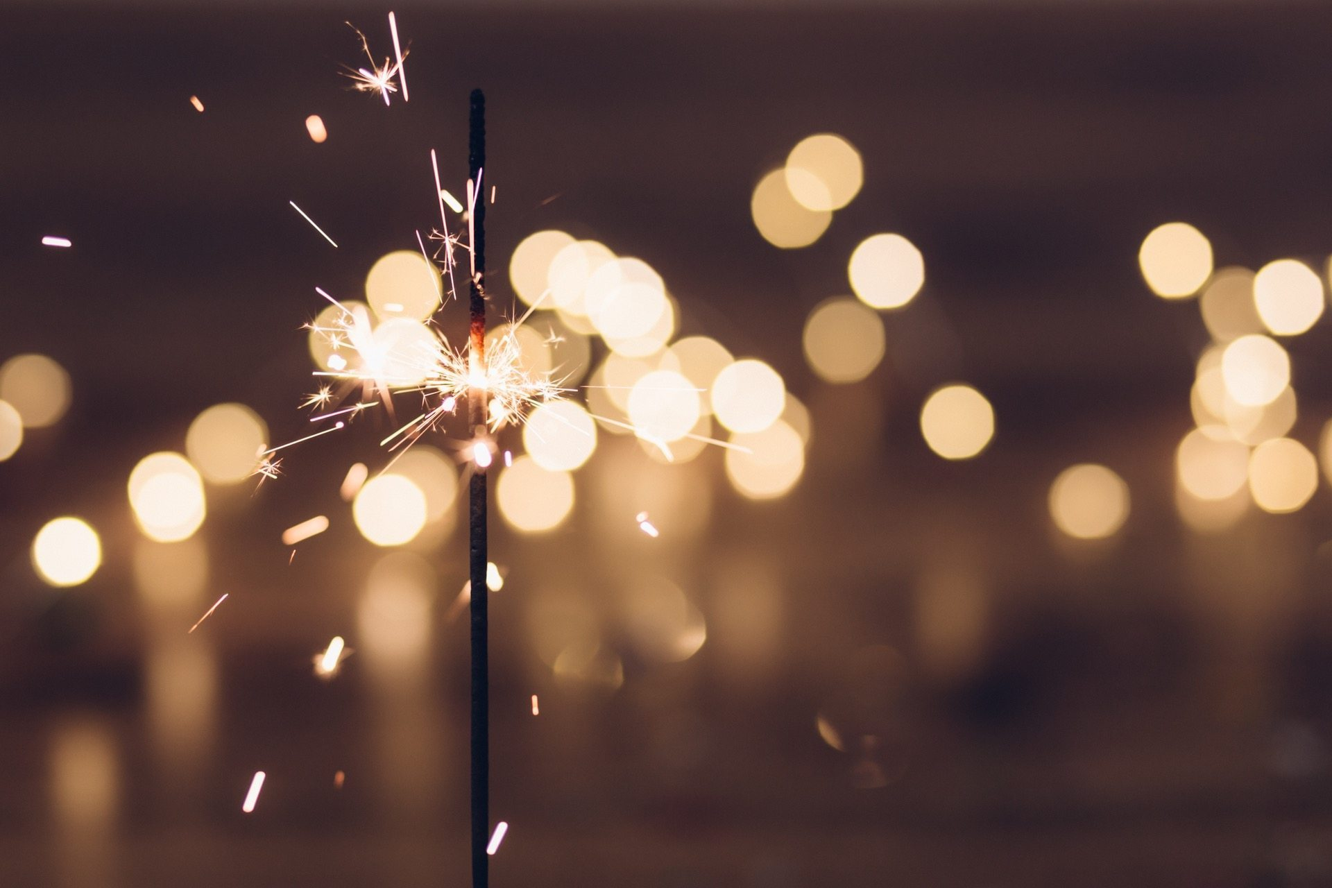 Image: sparkler at night with lights in the background