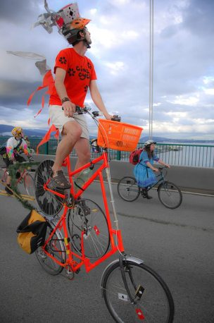 Image: Man in a bright orange top hat, on a bright orange bike sitting 10 feet in the air.