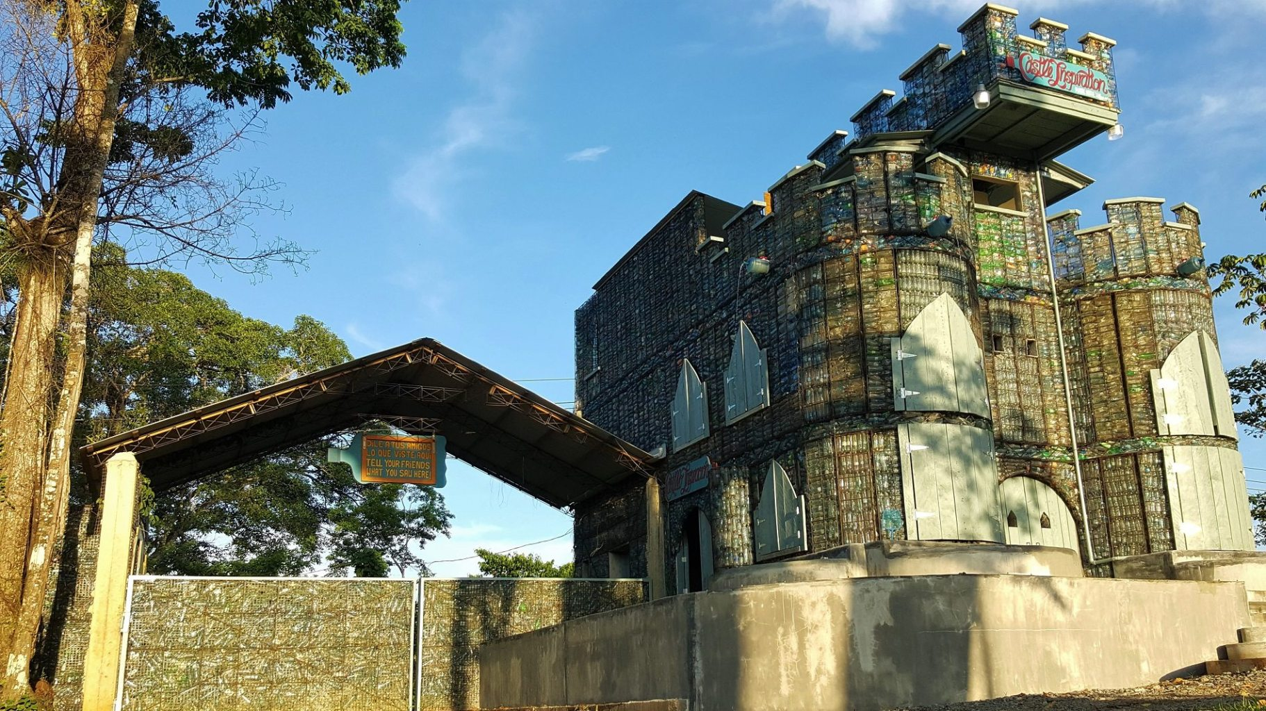 Image: Entrance to the plastic bottle village next to a castle. Both made out of bottles!