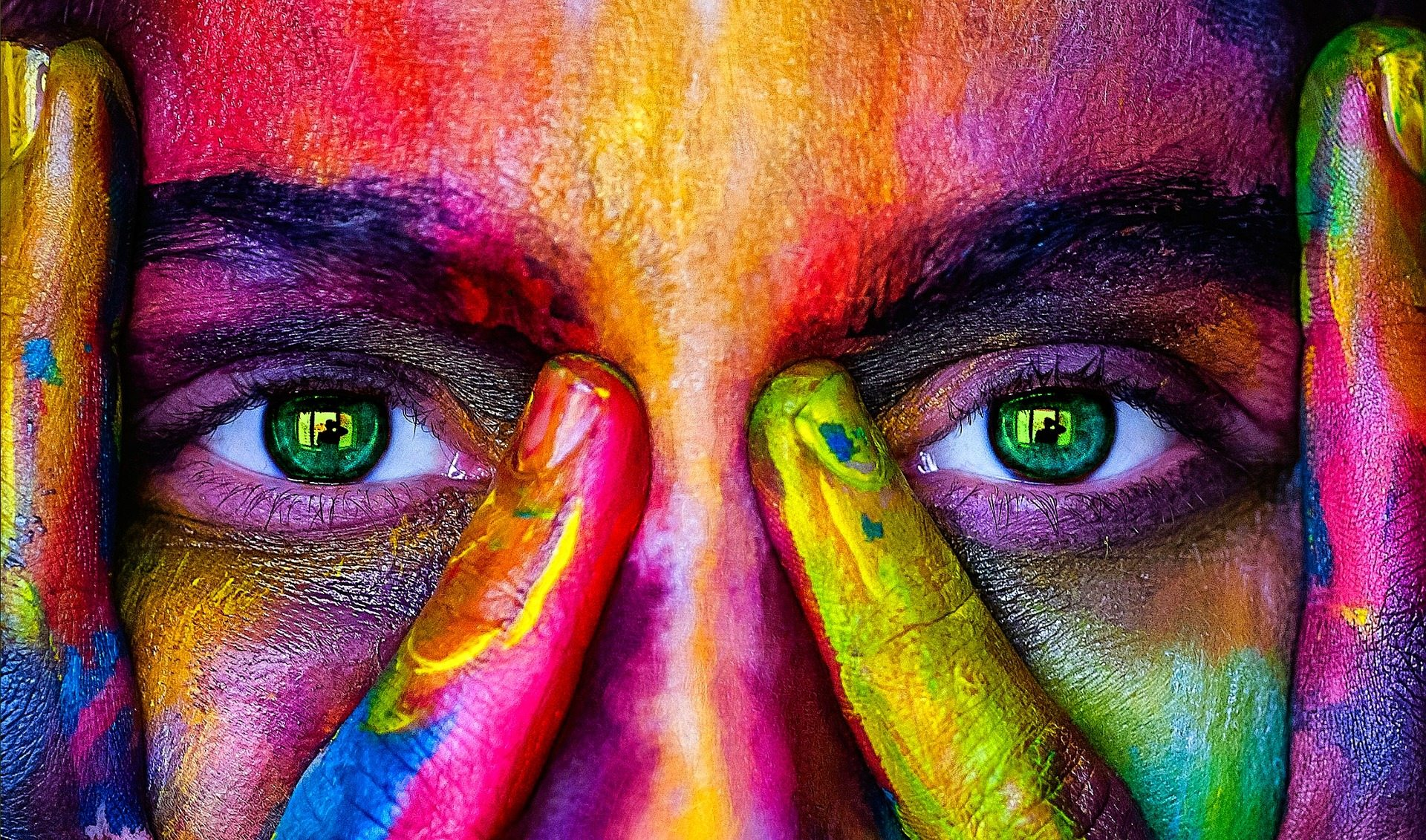 Image: woman's face with brightly colored paint on it