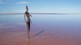 Image: Slender spartan sculpture of a woman standing a remote shallow water