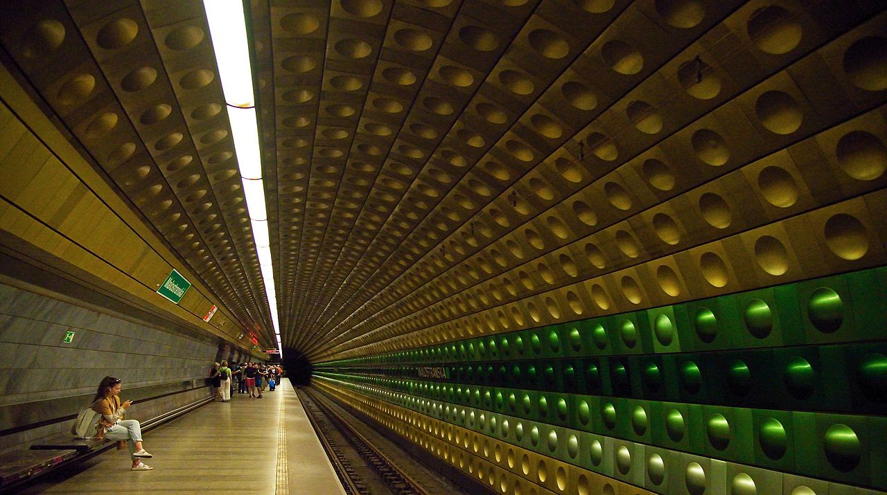 Image: A woman sits in a space-age looking subway station