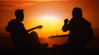 Image: two musicians playing guitar against sunset