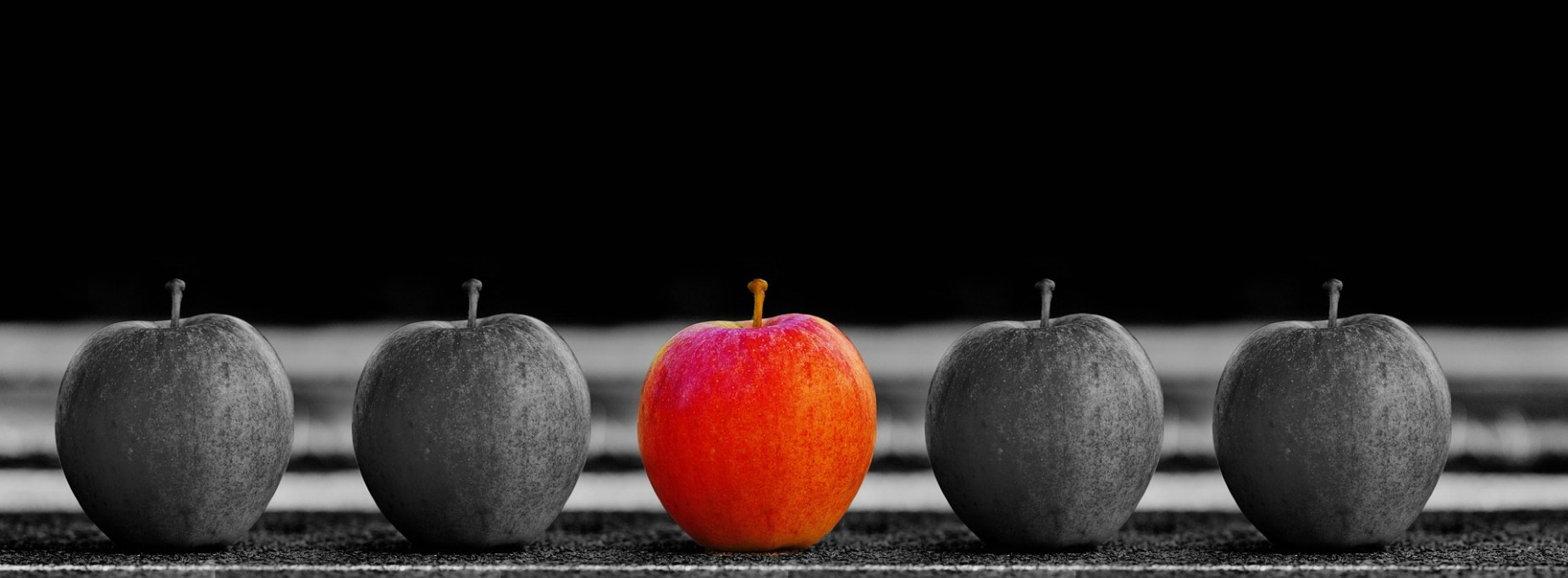Image: Black and white apples with a red apple in the center