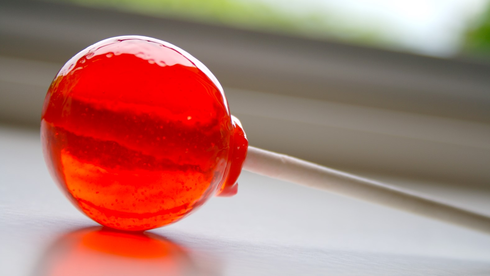 Image: A red lollipop lays on a counter-top reflecting light. One of our favorite motivational speakers, Drew Dudley, takes us through the power of giving lollipop moments.