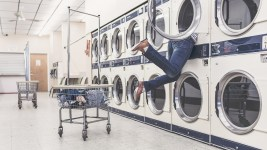Image: Woman reaching into the back of a washing machine