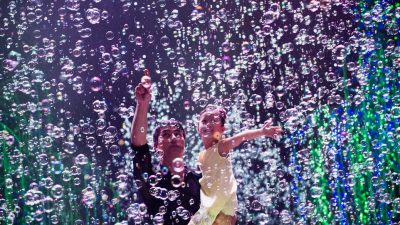 Image: Fan Yang holding child in the middle of bubbles!