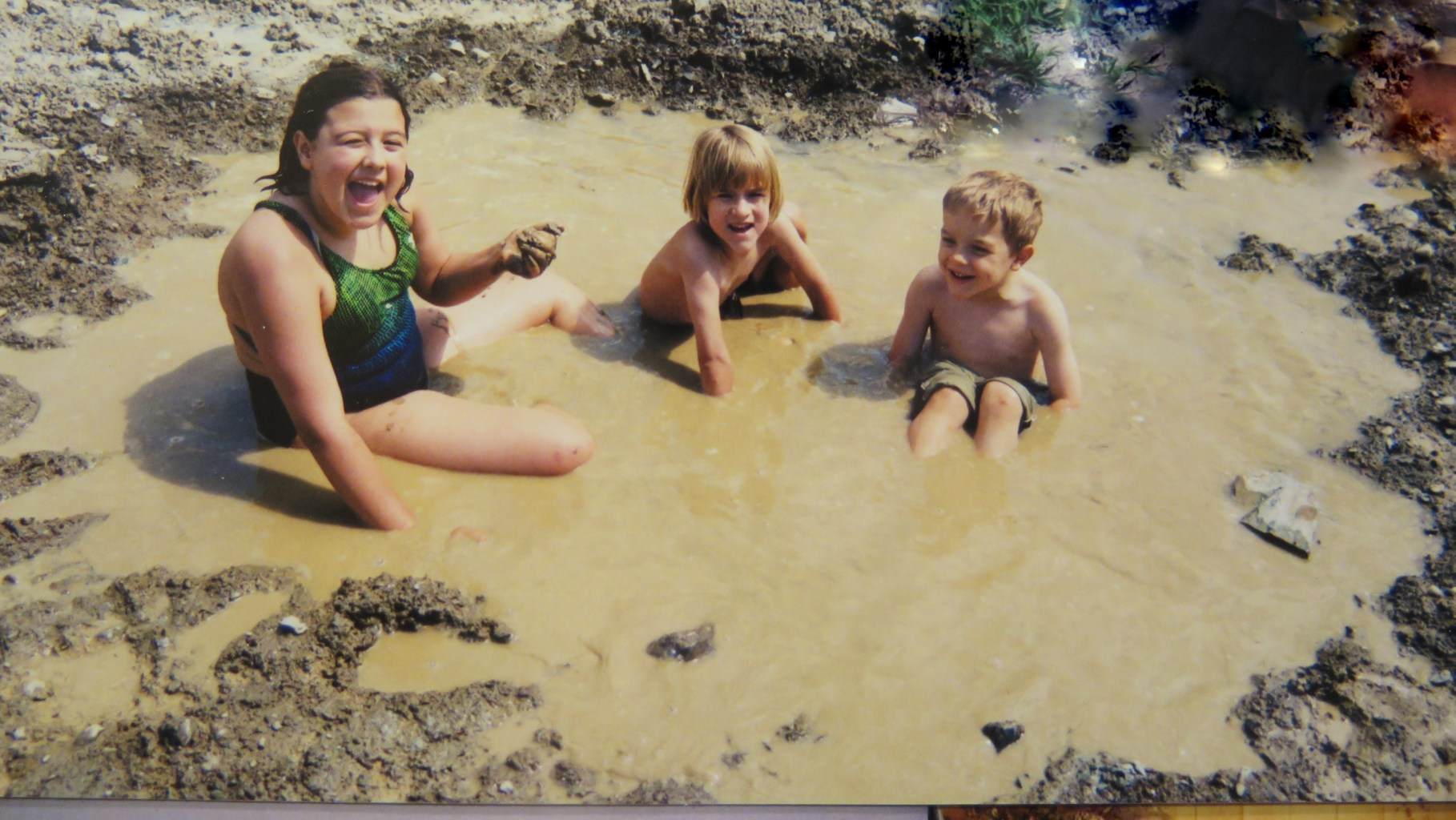 Image: Three small children delightfully sitting in a deep mud puddle