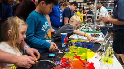 Image: Children working on a problem at a makers faire