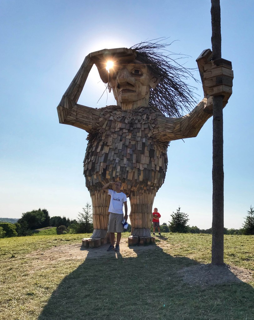 Image: A Troll made out of recycled wood stands 10 meters high in the sunshine.