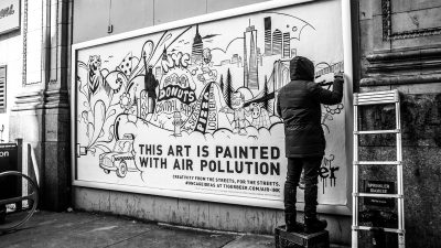 "Image: Artist completing a mural in NYC of a skyline and the text ""This art is painted with air pollution"""