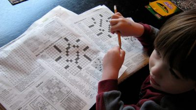 Image: child sitting in front of two crossword puzzles pretending to solve them