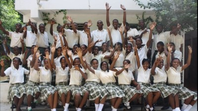 Image: Dozens of students in school uniforms celebrate graduation
