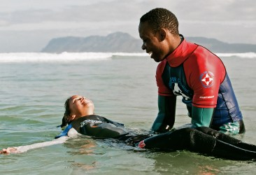 Image: A child smiling and laying on their back in the ocean while a coach lifts them up