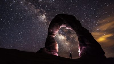 Image: Man standing underneath a rock arch looking up at the stars of the night sky