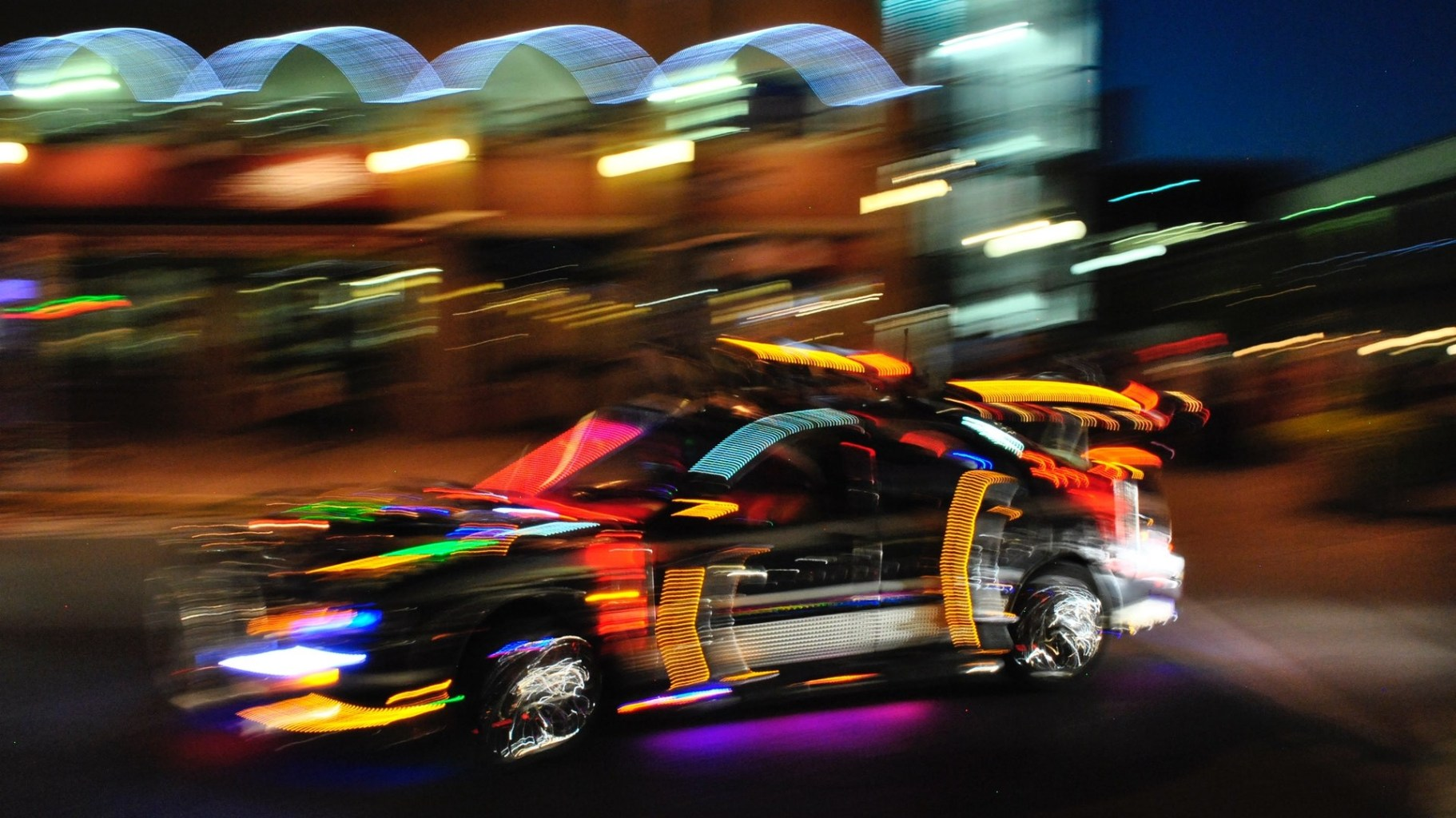 Image: Race car at night with blurry and colorful light