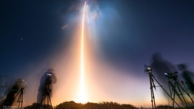 Image: spacex launch streak of light on a dark cloudy sky
