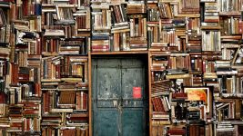 Image: Books stacked along a wall, lining a doorway