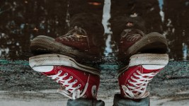 Image: The reflection of red sneakers in a puddle, looking upside down.