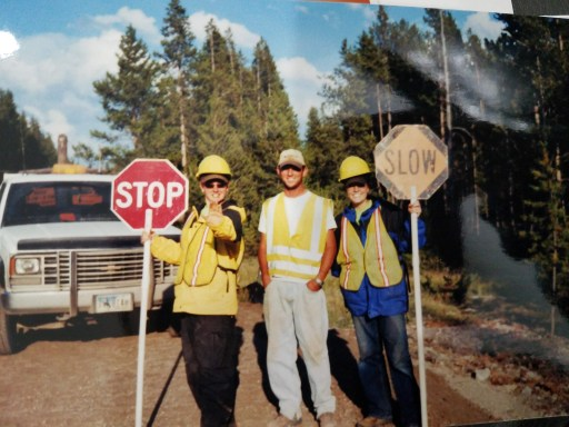 Brittney in her construction outfit holding a stop sign with two friends