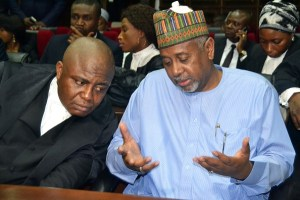 "Former national security adviser of ex-president Goodluck Jonathan, Sambo Dasuki (R), speaks with his lawyer Ahmed Raji, during his trial at the federal high court in Abuja, on September 1, 2015. Nigerian prosecutors on September 1, 2015 slapped a charge of unlawful possession of arms against Dasuki. Dasuki was arraigned on a ""one-count charge of being in possession of firearms without licence,"" Prosecutor Mohammed Diri told the federal high court in Abuja. AFP PHOTO/STRINGER (Photo credit should read STRINGER/AFP/Getty Images)"