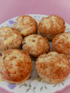 Seven cheese scones on a flowered plate sitting on a pink tablecloth