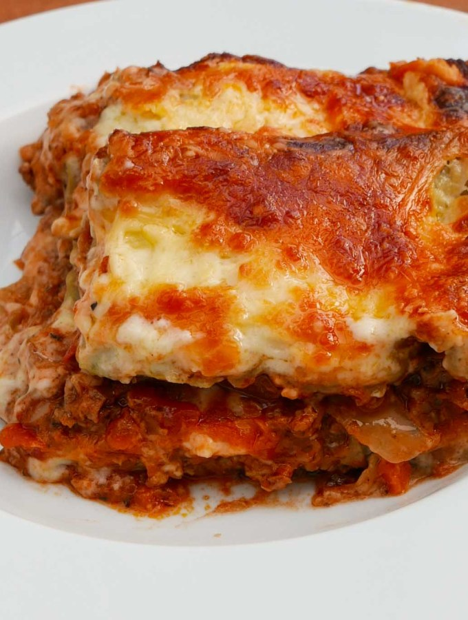 A slice of lasagne in a white bowl, showing layers of meat, pasta and cheeses sauce topped with grated cheese.