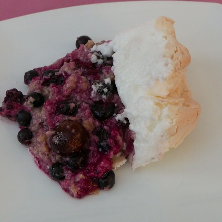 A portion of Black Forest Meringue Pudding on a white plate.