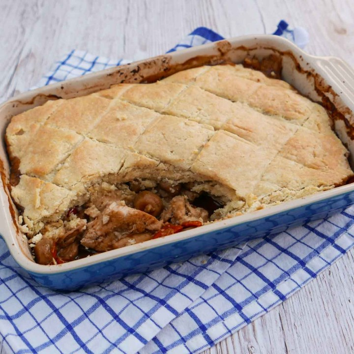 Chicken Cobbler in a blue gratin dish with a portion removed.