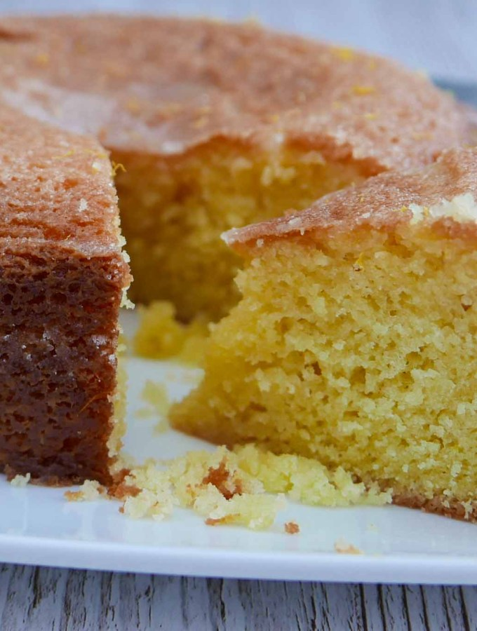 A large Lemon Drizzle Cake with a slice cut to show the moist centre