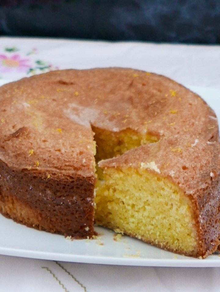 A lround Lemon Drizzle Cake with a slice cut to show the lemon-soaked centre