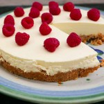 Easy Lemon Cheesecake on a plate with a slice on a small plate