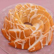 Lemon Bundt Cake with lemon drizzle icing on a glass plate