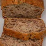 Two slices of Banana Loaf on a grey plate with the rest of the cake