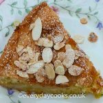 A slice of Pear and Almond Cake on a patterned plate
