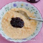 Slow Cooker Rice Pudding in a bowl with raspberry jam.