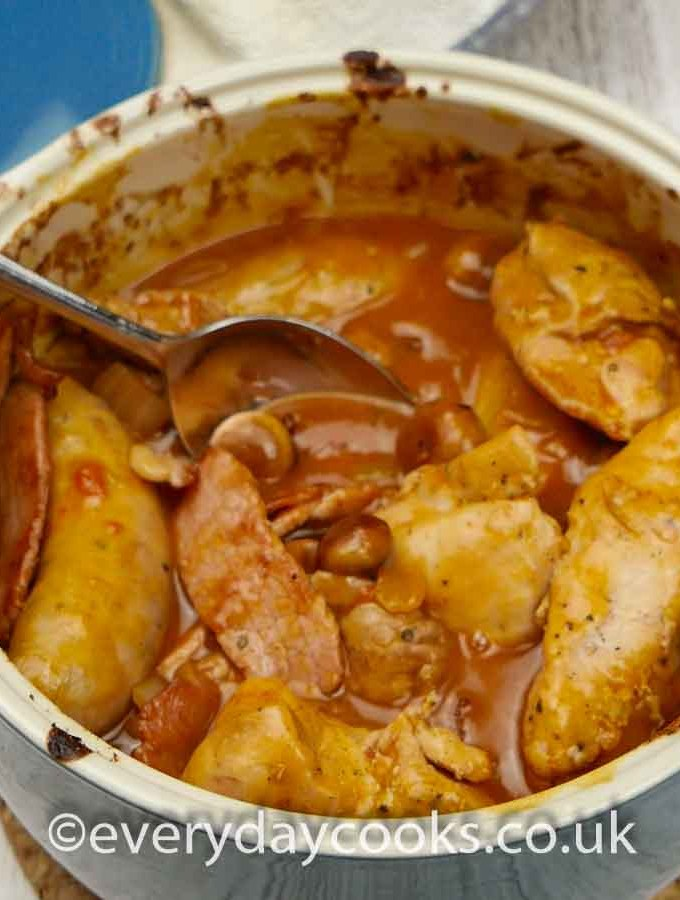 Chicken Chasseur in a blue casserole dish with a spoon