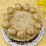 Light Simnel Cake on a patterned plate on a yellow cloth