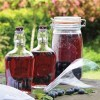 Kilner jar and two bottles with Sloe Gin on a wooden table