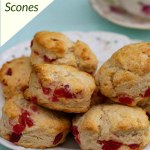 A plate of Cherry Scones with a teacup in the background on a blue cloth
