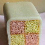 Easy Battenberg Cake with a slice cut, on a pink cloth