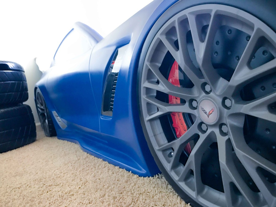 A closeup of the tires of a blue race car bed for a toddler